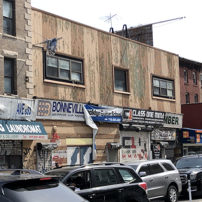 many commercial banners on a storefront that's made of peeling wooden